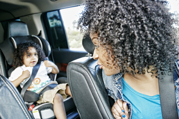 Mixed race and mother checking daughter in car seat