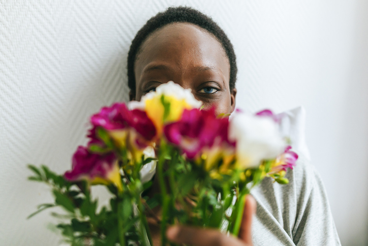 Portrait of woman behind flowers
