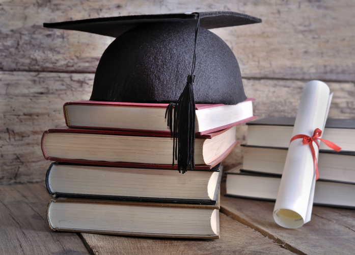 Close-Up Of Books And Mortarboard With Certificate On Table