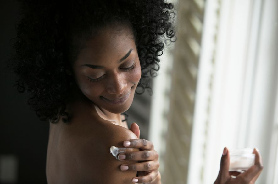 Woman Applying Lotion to Her Shoulder