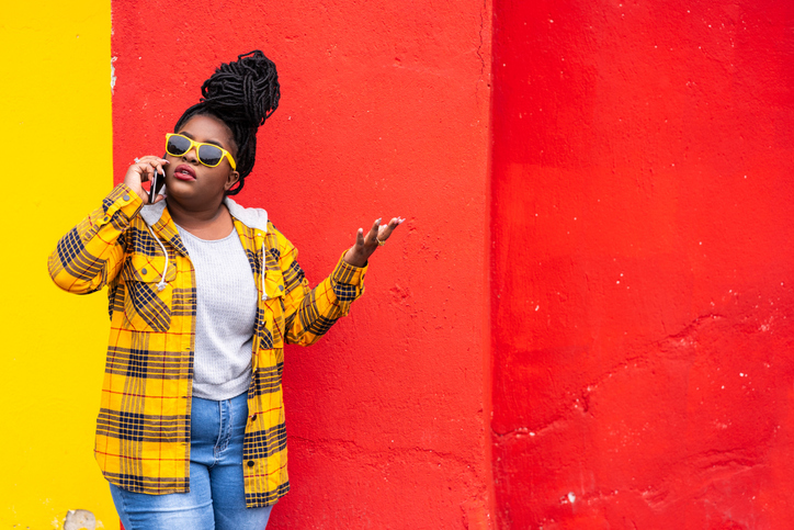 Afro woman on colorful background talking on a smartphone