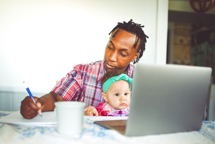 African American dad works on a computer with his infant daughter work from home modern masculinity
