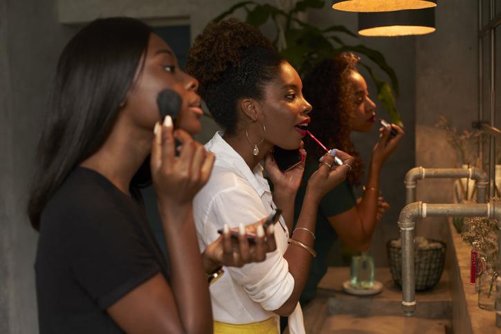 Three friends applying makeup at ladies' room