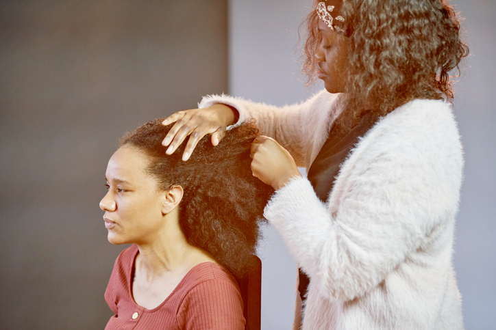 A woman having her natural afro hair groomed