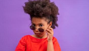 Ethnic kid girl looking camera lowering sunglasses