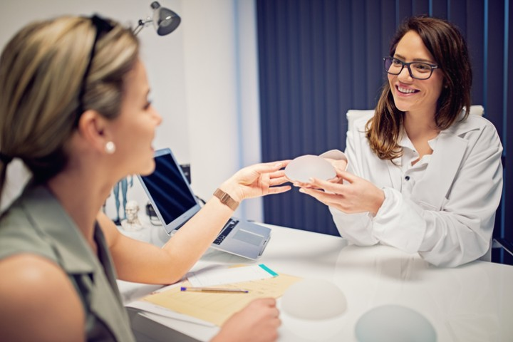Doctor is showing breast implants to young woman in beauty treatment clinic