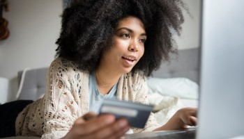 African American woman laying in bed online shopping with laptop