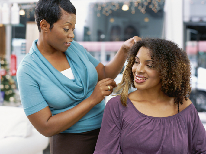 Close-up of a young woman and her hair stylist