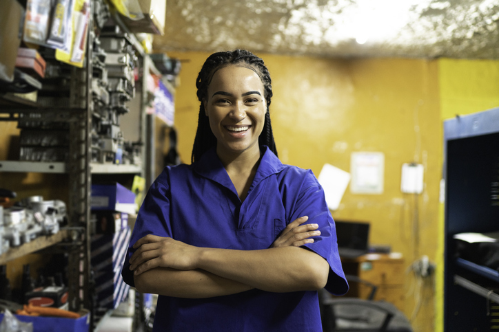 Portrait of a female mechanic with arms crossed in a auto repair shop
