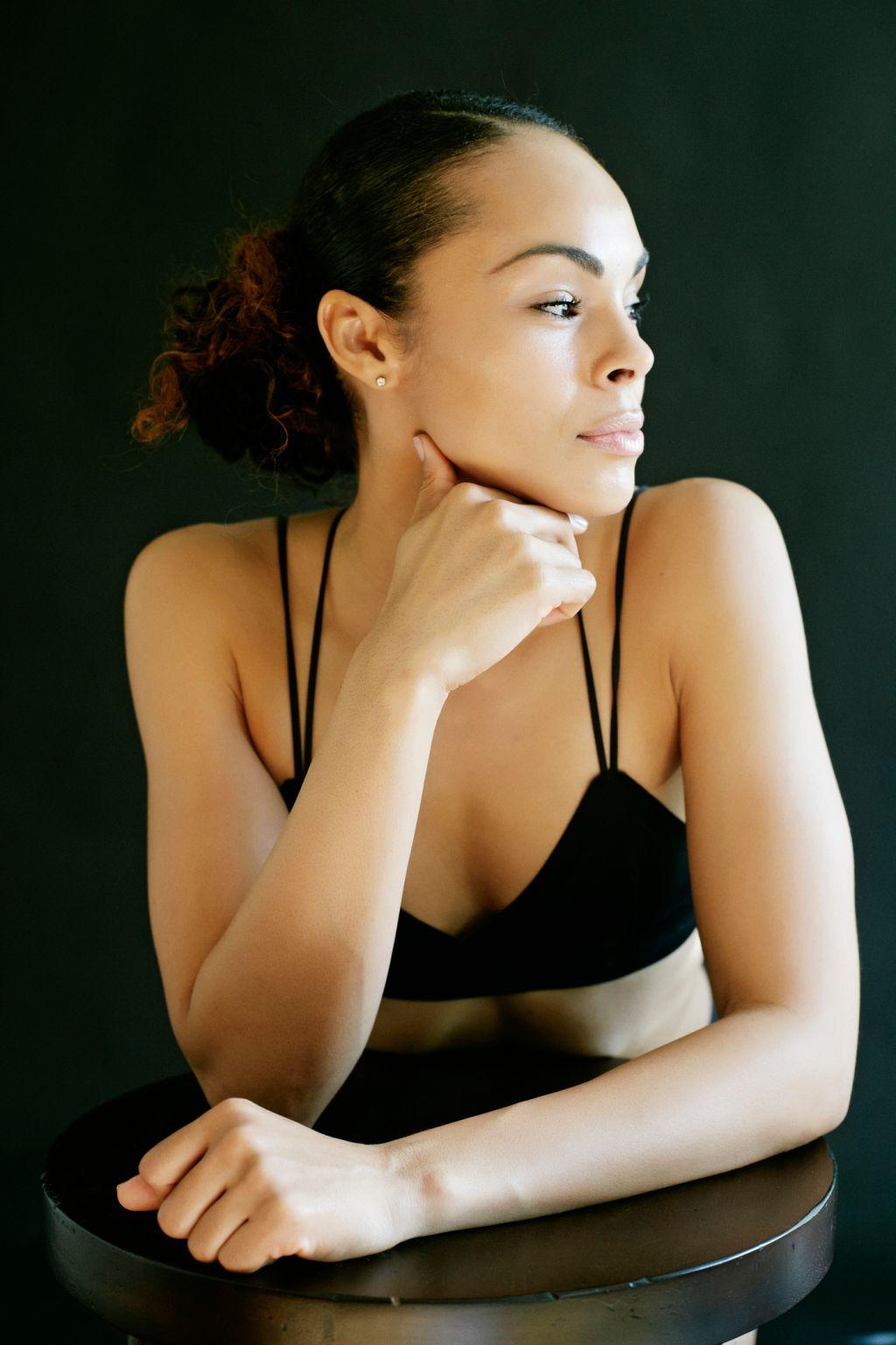 Pensive Mixed Race woman wearing bra leaning on stool
