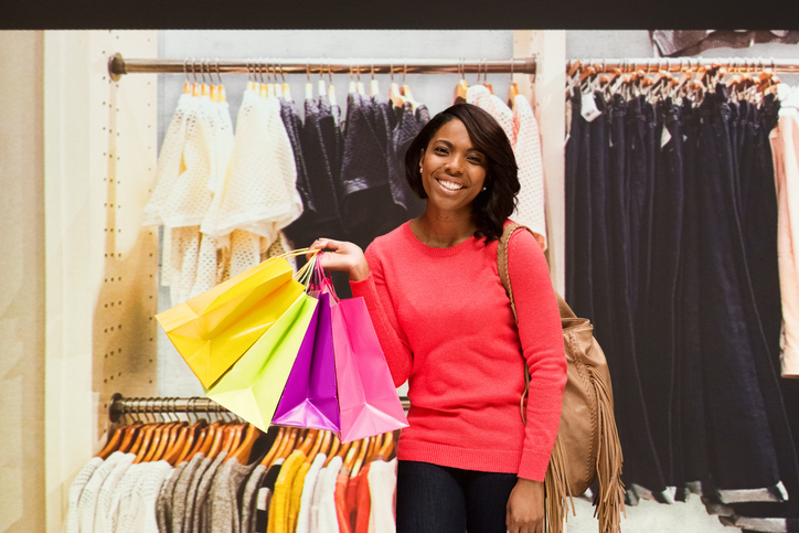 Smiling woman holding shopping bag indoors