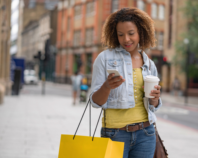 Shopping woman on the street using her mobile phone