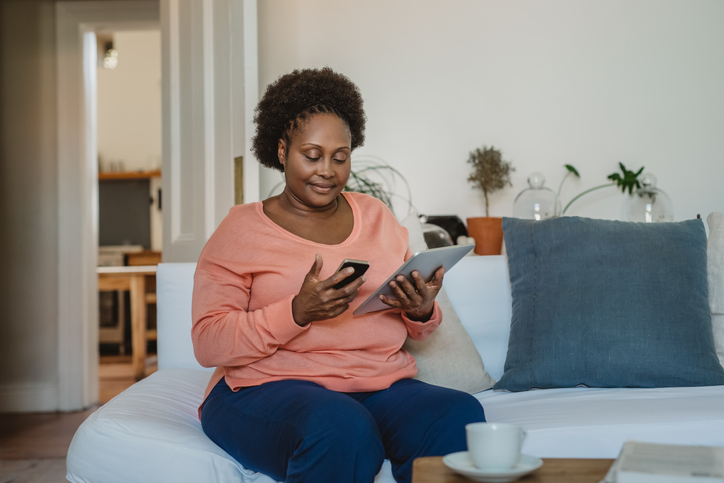 Smiling African American woman browsing online with a digital tablet
