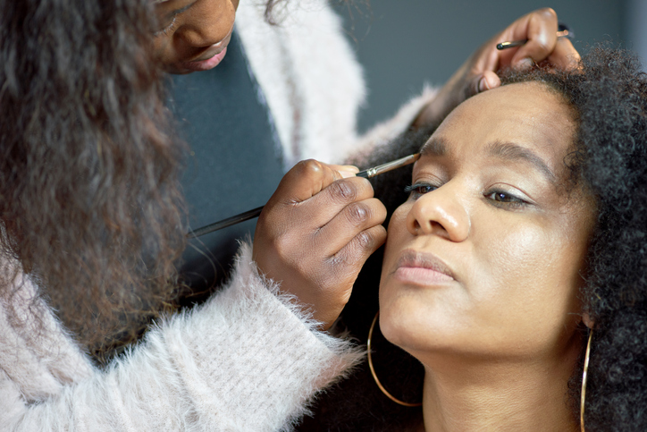 A make-up artist applying make-up to the face of her client