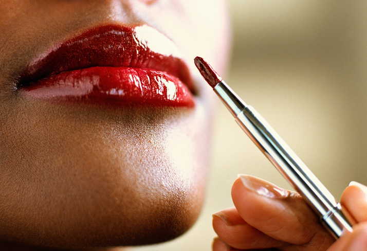 Woman applying lipstick with brush, close-up