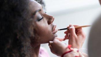 Makeup artist applies lipstick