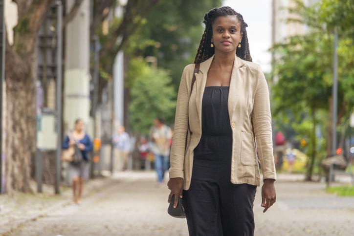 Black brazilian woman walking on the sidewalk