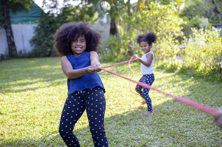 Children play with mom in the home garden. They pull the rope and have fun happy together.