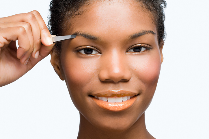 Young woman plucking eyebrows