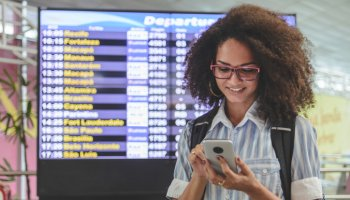 Young woman checking her boarding schedule at smartphone with airport departure time board on background