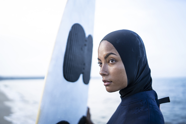 Young woman with hijab holding surfboard on beach