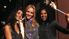Portrait Of Cheerful Female Friends With Sparklers In City At Night
