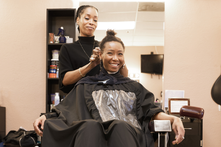 Female hairdresser combing woman's hair