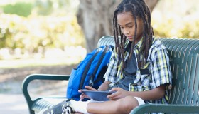 Boy (13-15) sitting on bench with tablet
