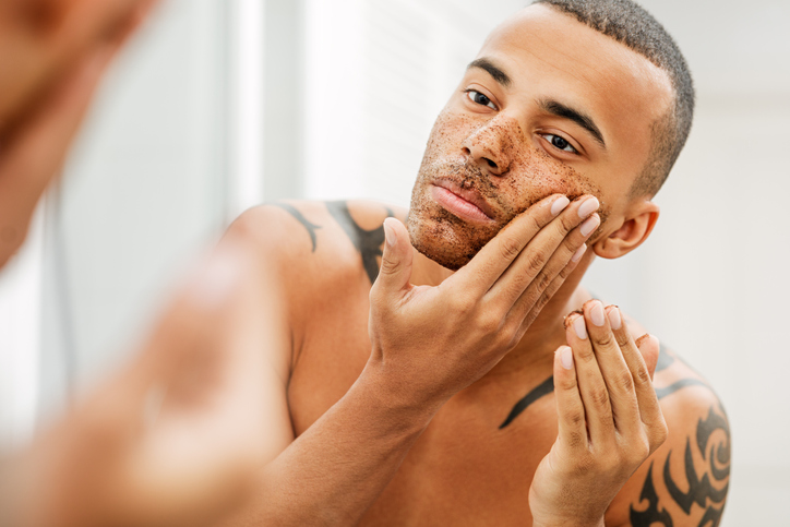 Shirtless Young Man Applying Facial Mask Reflecting On Mirror In Bathroom At Home