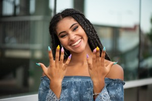 Cheerful fashion girl posing with multicolored nails