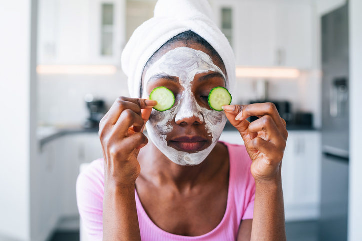 Beautiful young afro woman with cucumber on eyes
