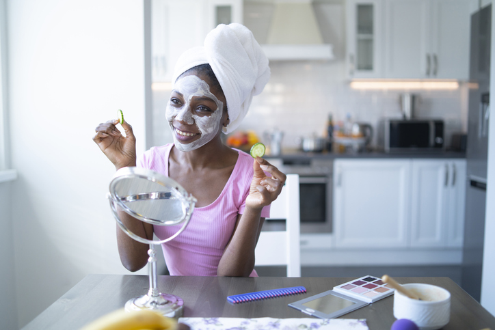 Smiling african woman with facial mask and towel on head, at home