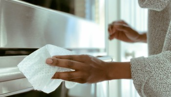 Woman Cleans Oven Handle Using Disinfectant Wipe
