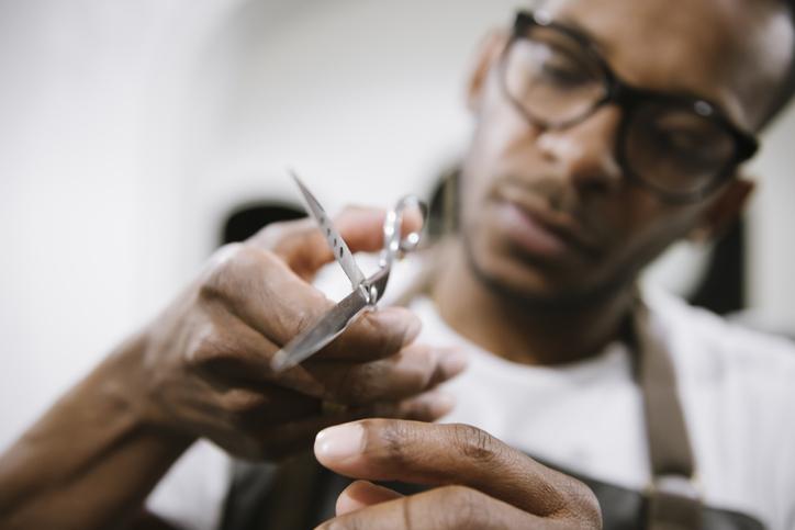 Close-up of barber holding scissors