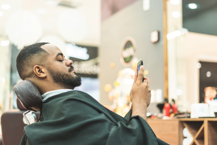 African man using cell phone in barbershop
