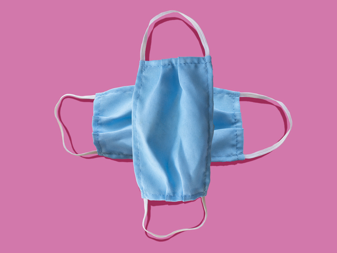 Blue medical face mask to avoid contagious diseases pattern on pink background