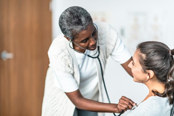 Female Doctor Examines Patient stock photo
