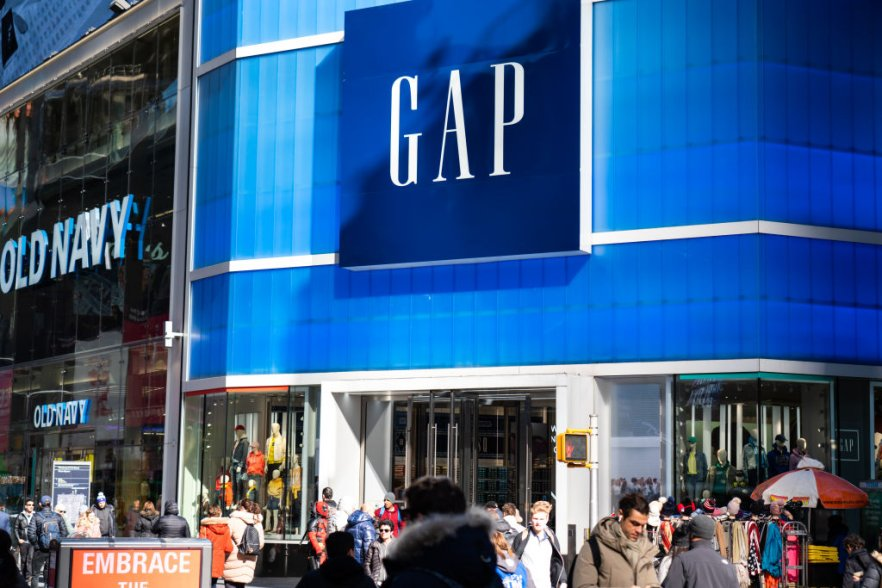 Pedestrians walk past an American worldwide clothing and...
