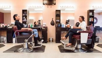 Two women sat drinking coffee in a hair salon
