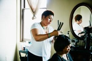 Salon owner straightening hair of client in salon