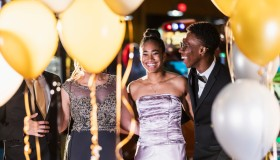 Teenage couple with friends having fun at prom