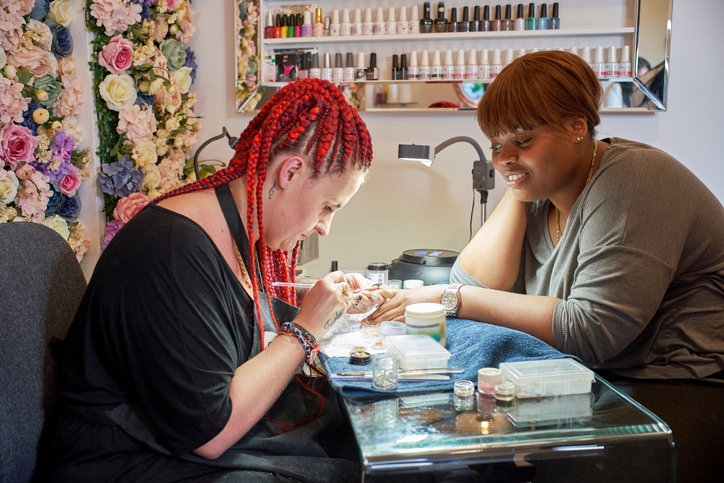 A nail artist and her client having her nails manicured.