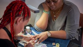 A close-up of a nail artist creating a chandelier nail manicure