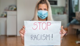 Young woman with face mask (I Can't Breathe) holding a poster with a message: STOP RACISM!