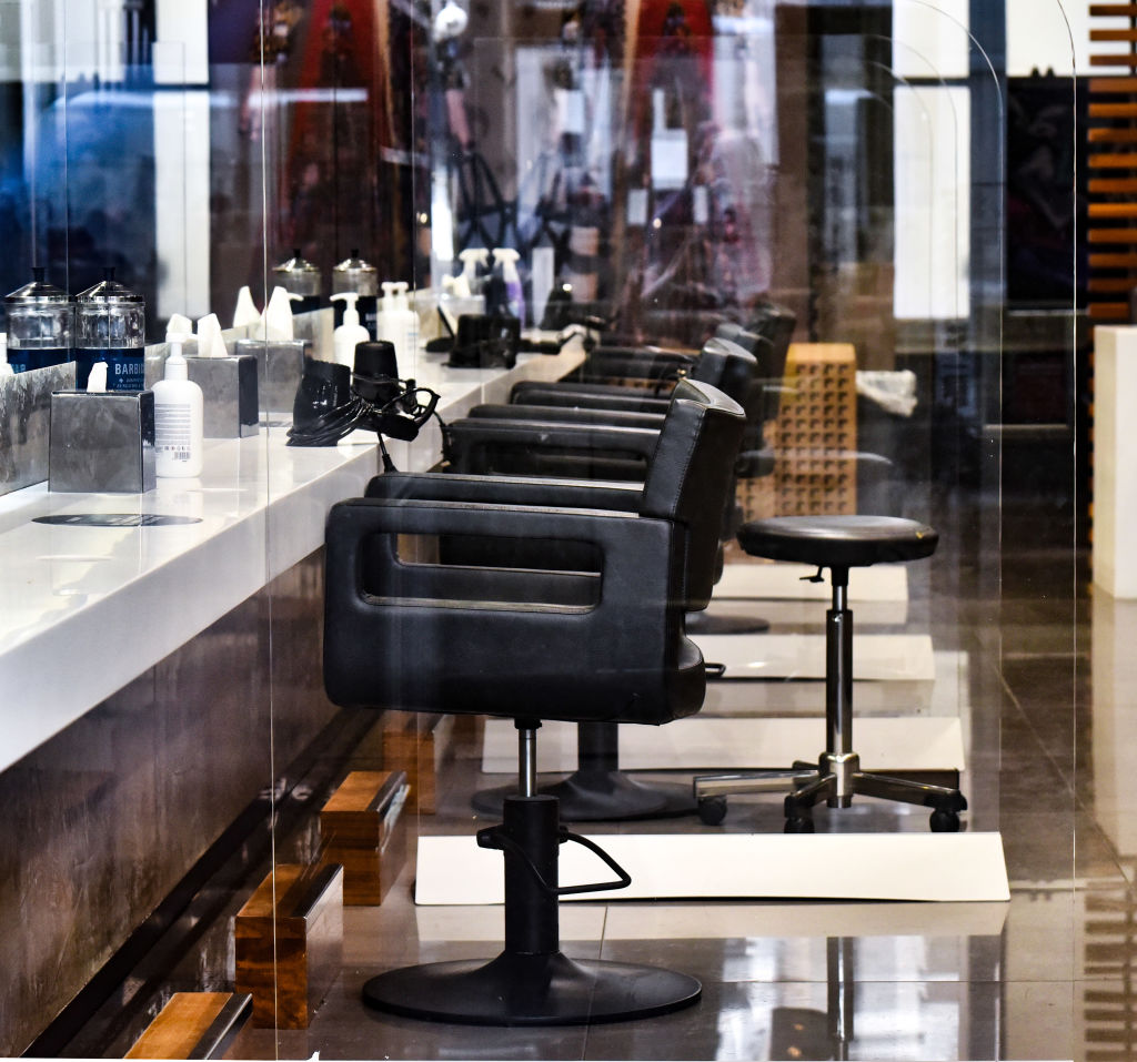 Perspex screens separating chairs in a hair dresser's salon...