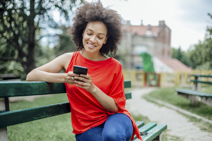 Happy African American female using a smart phone