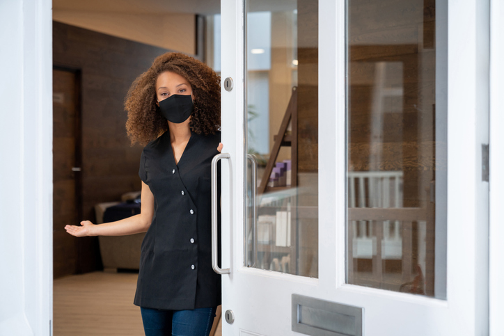 Business owner opening the door of her spa wearing a facemask