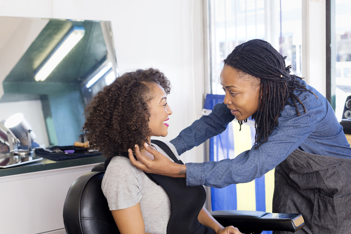 Female barber styling customers ringlets in barber shop