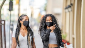 African American sisters shopping downtown wearing masks