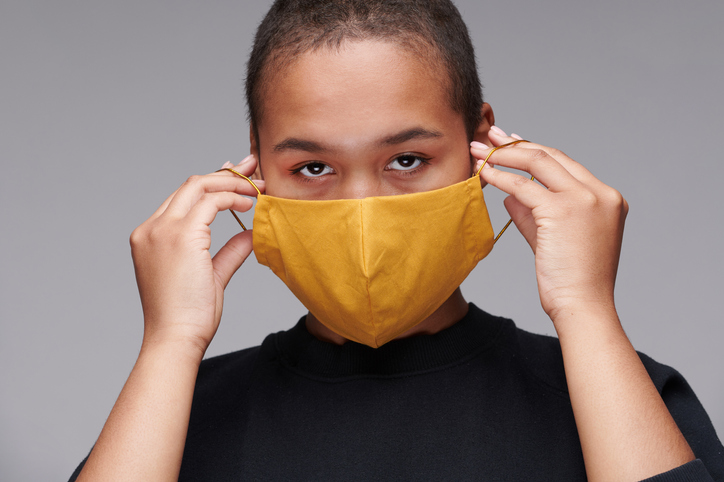 Portrait of young Black woman wearing yellow mask to protect herself against coronavirus